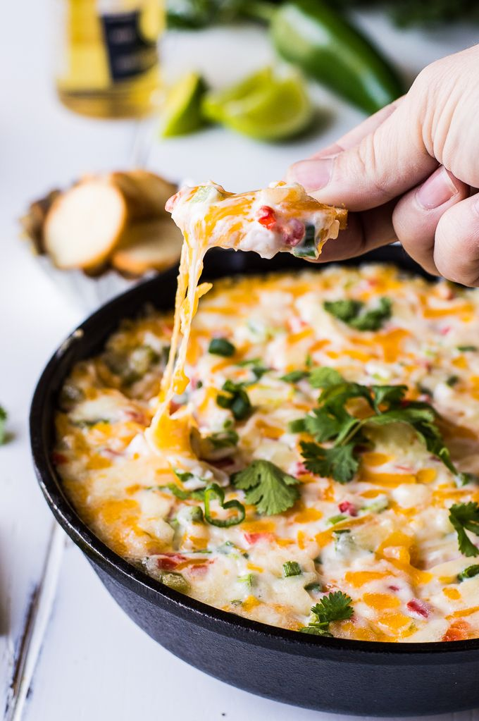 Tex Mex style Hot Pimento Cheese Dip is the ultimate in hot cheese dip recipes! Loaded with sweet pimento peppers, jalapeños, cumin, and topped with some cilantro. This cheese dip is sure to disappear FAST!