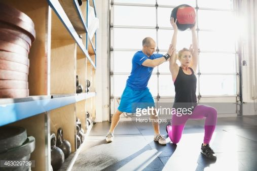 Stock Photo : Gym instructor assisting woman with medicine ball lunge