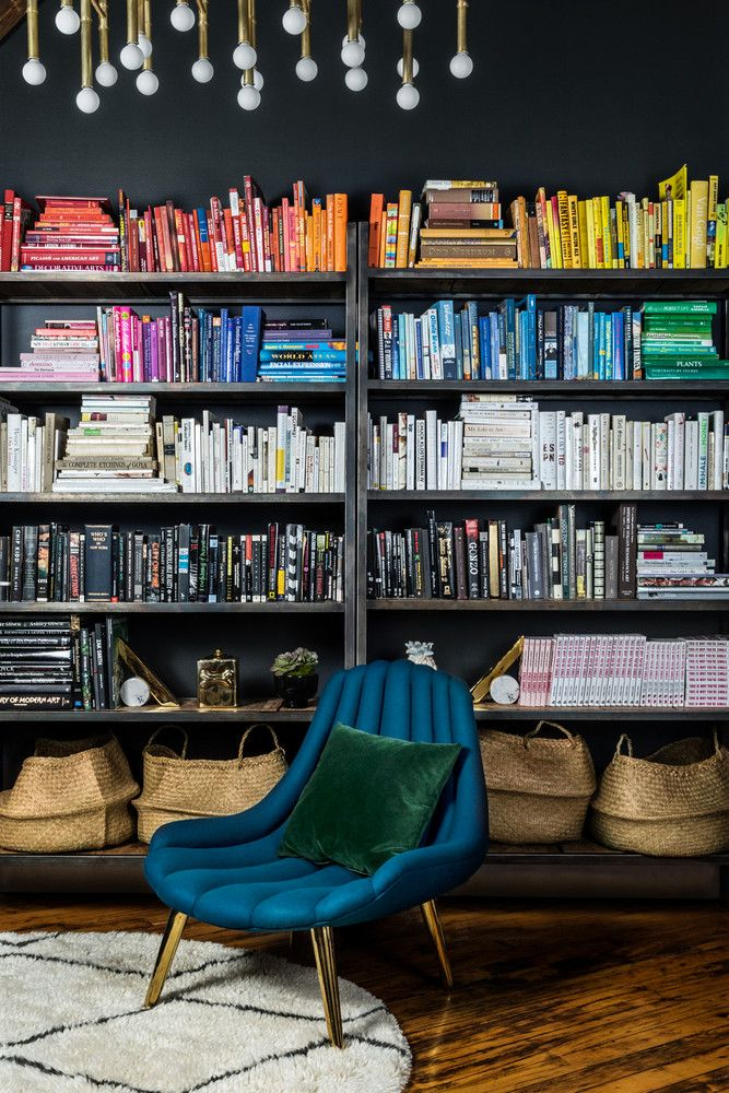 In the office, a color-coded approach to the book display invites a vibrant wealth of personality to the otherwise dark scheme