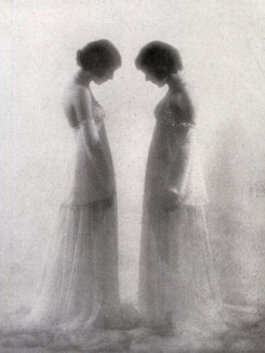 Full-length portrait, in profile, of two girls. The lovely young women are dressed in identical elegant white evening dresses and have their hair gathered up. They are facing each other as if they were mirror images. The luminous background and the strong pictorial blurring create a poetic and reflective atmosphere, Library of Fratelli Alinari Museum of the History of Photography, Florence