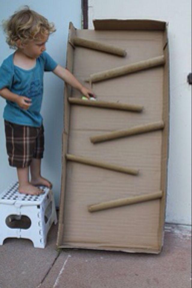 Je neemt een kartonen doos en plakt  daar allemaal halve pvc buizen in of kartonen keukenrolletjes. Deze plak je er dan kris kras onder elkaar zodat he balletjes naar beneden kan rollen.