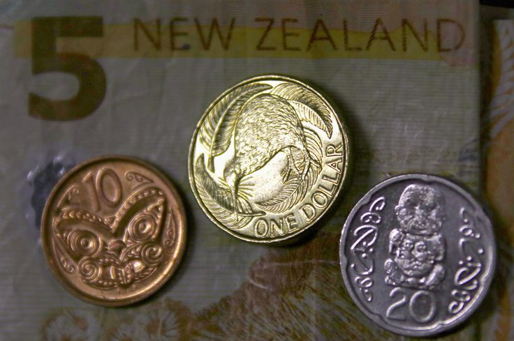 A New Zealand dollar coin sits next to other coins and atop a five-dollar note. (Reuters Photo/David Gray)