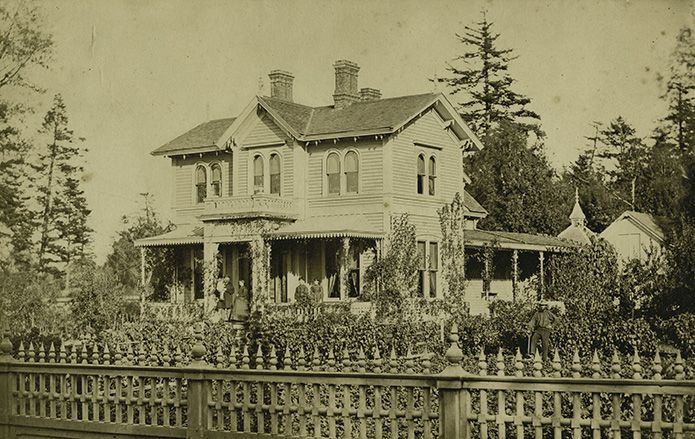 """""""The house was large and well-built, of California redwood, the garden prim and carefully tended. Everything about it was extremely English."""" – Emily Carr. The Carr family residence, with Richard, Emily (Saunders) Carr, and children assembled on the front porch, c. 1869."""