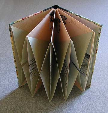 """Origami folded book by Karen Elaine Thomas. This book was made with more neutral colors to offset the content as an idea for the projects in Origami Card Craft. Sage green and soft peach rice papers were cut 6"""" square and stamped with black ink before folding and gluing. The covers were made with book binding boards and decorative paper which were glued to the front and back of the folded book for a more finished look."""