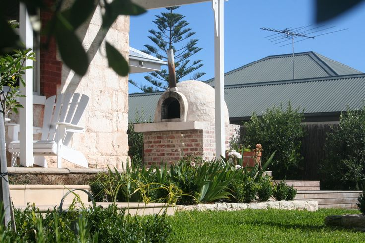 Local limestone wood fired Pizza oven on recycled brick base with concrete hearth. Blairgowrie House www.marktraversla.com
