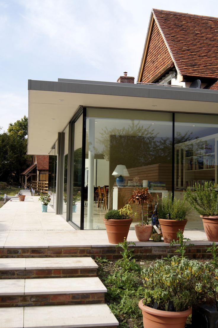 Flat roofed and glass walled extension to traditionally built house