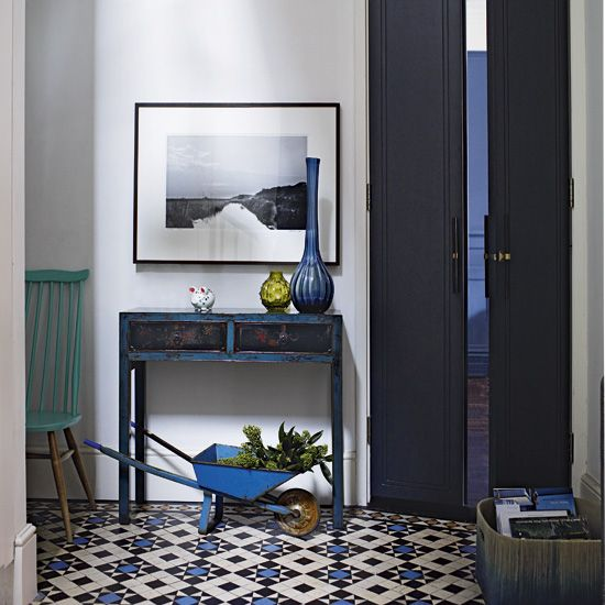 Hallway with Victorian-style floor tiles and blue console table