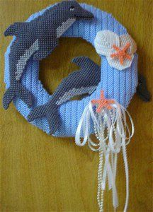 The Dancing Dolphin Door Wreath. Dolphin lovers everywhere check this out !! This pretty blue wreath has 2 comical & playful dolphins & is also trimmed with seashells & pearls.