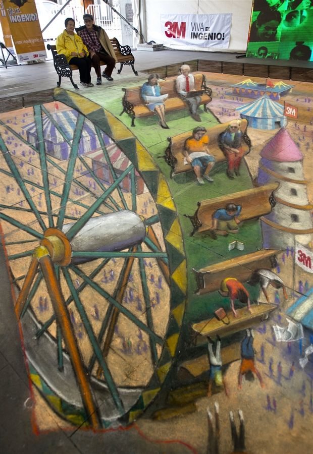 Chilean people pose on the work of British artist Julian Beever, who specializes in pavement drawings, wall murals and realistic paintings, on May 3rd in Santiago, Chile.