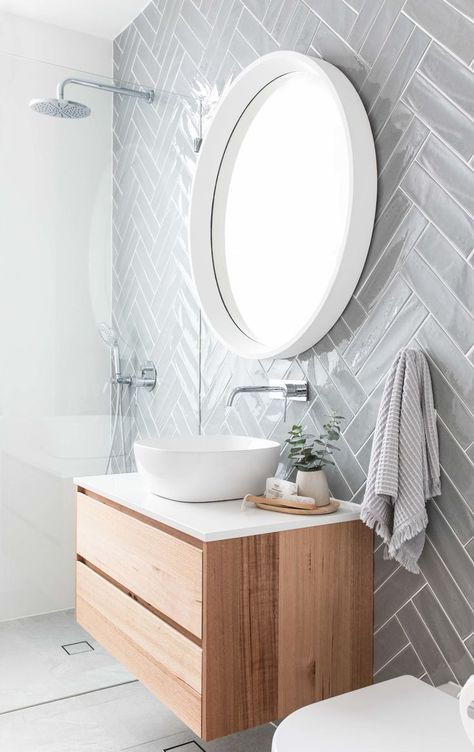 Gray herringbone subway tile on modern bathroom with floating vanity, white vess
