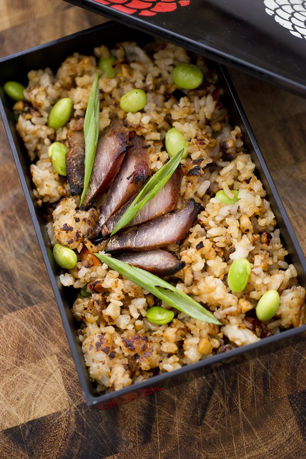 """bentocharsiu"" - The contents are sushi rice pan-seared to a lovely crisp with a glaze of miso, tamari and mirin, then tossed with shelled edamame. The topping is homemade Chinese barbeques pork and scallions."