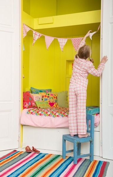 Bed in a closet... hey, I used to have one of these! Love the bright colors and rug.