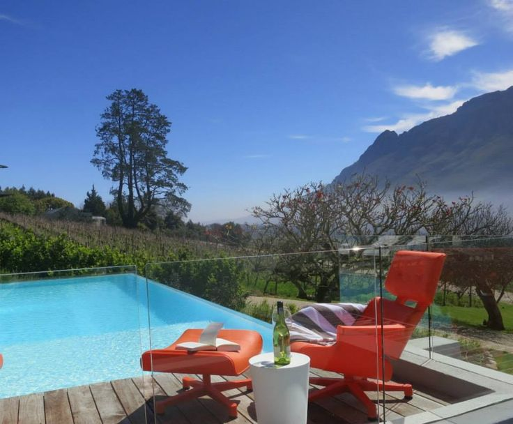 What more could you need on a summer's day than a glass of Clouds wine, a pristine pool and beautifully unique orange furniture? #Cloudsestate #stellenbosch http://cloudsestate.com/home-26.html