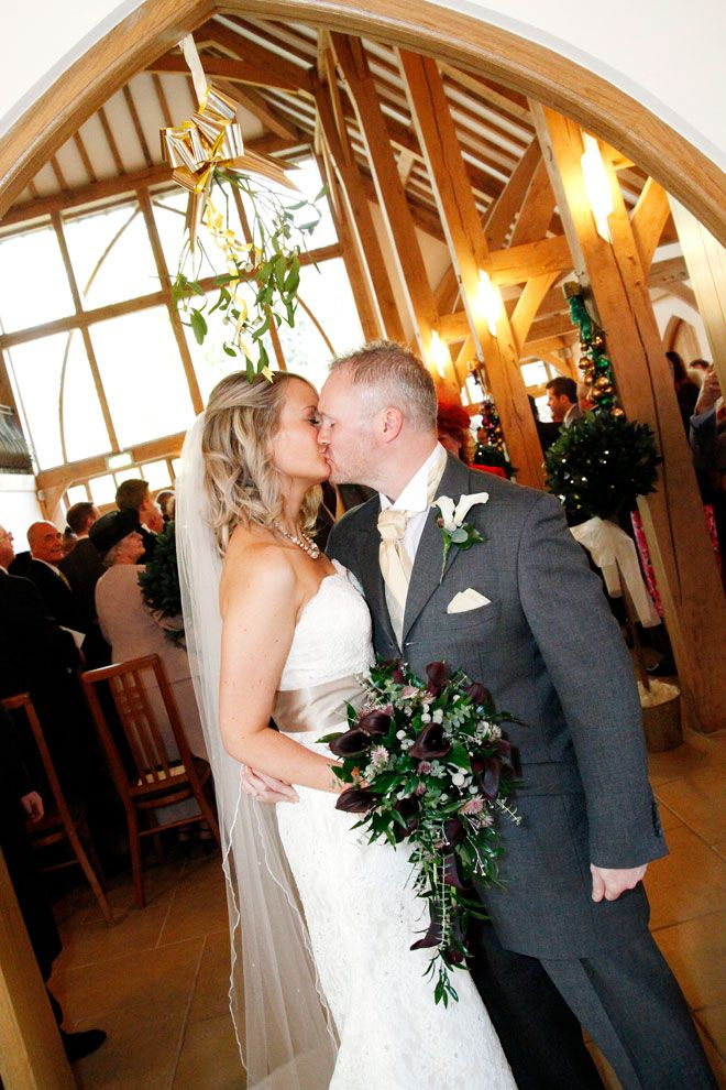 Bride and groom kissing beneath the mistletoe at a Rivervale Barn Christmas wedding | www.allabouttheimage.co.uk