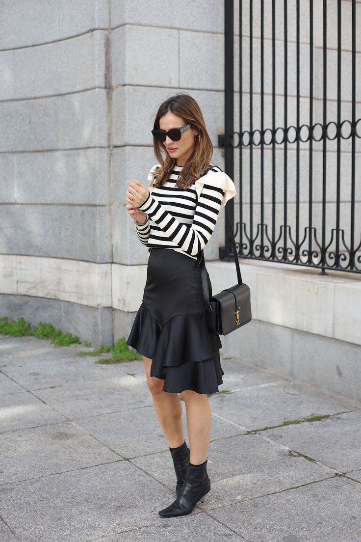 ruffle top looks - Lady Addict. Black and white streiped ruffle top+black ruffle asymmetric satin skirt+black kitten heeled ankle boots+black shoulder bag+black coat with golden buttons+black sunglasses. Winter Dressy Casual Outfit 2017