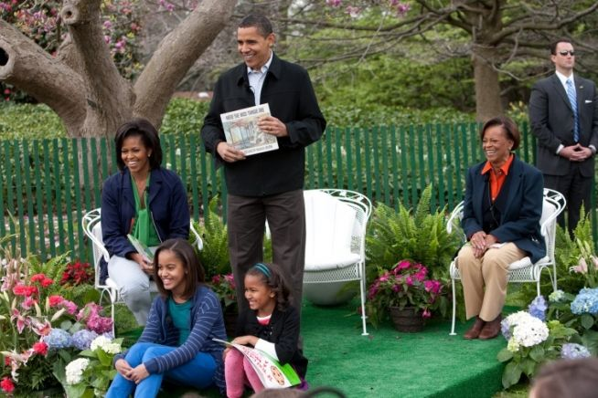 President Obama,joined by First Lady Obama,their daughters,Sasha and Malia ,and Michelle Obama's mother,Marian Robinson, prepares to read a story,to children at the White House Easter Egg Roll.,4/13/2009.