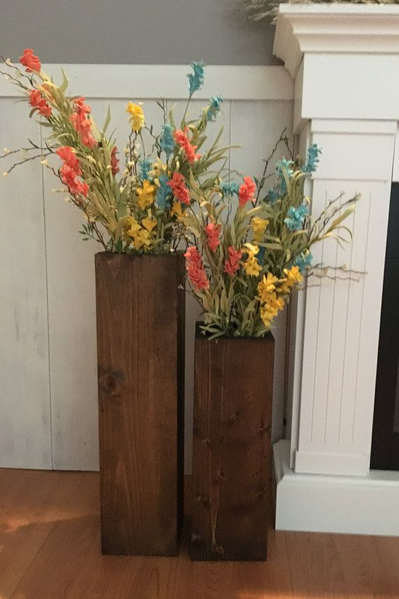 This set of 2 large floor vases will add a little rustic charm to your porch or living room! The large vase measures 24 x 6 and the smaller one measures 18 x 6. These vases are made form reclaimed wood that has been sanded and stained a dark walnut. Looks great with large stems or