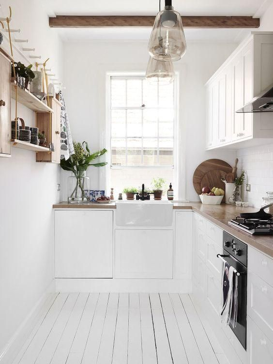 The Scandinavian inspired Sydney home of Frag and Naomi Woodall, with painted white wood floors, all-white upper and lower kitchen cabinets, butcher block counters, open shelves for a spice rack, and exposed reclaimed wood beams in the ceiling. Love this minimalist and organic inspired galley kitchen design!