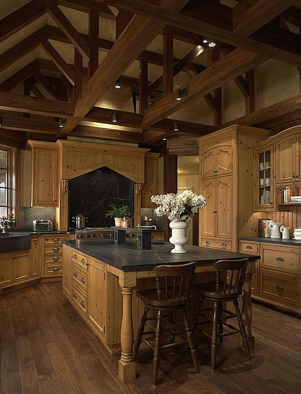 ** Singular tone of natural wood cabinetry unifies this kitchen, sandwiched between dark exposed ceiling beams and matching hardwood flooring. Black marble topped island commands the center.