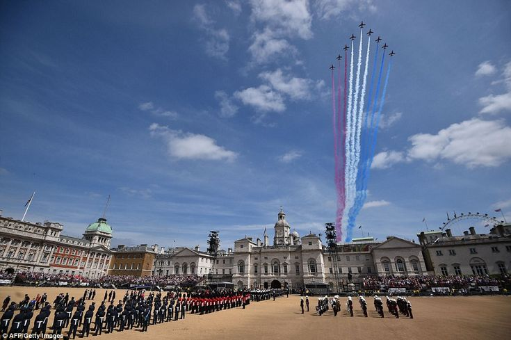 A fly-past of Second World War aircraft by the Red Arrows is watched by members of the arm...
