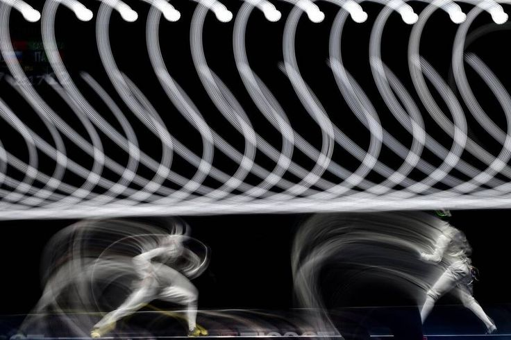 A picture taken with a long exposure shows Italy's Andrea Cassara (R) and Russia's Dmitry Rigin competing during the men's foil team gold medal match at the 2015 World Fencing Championships in Moscow on July 19, 2015. KIRILL KUDRYAVTSEV/AFP/Getty Images