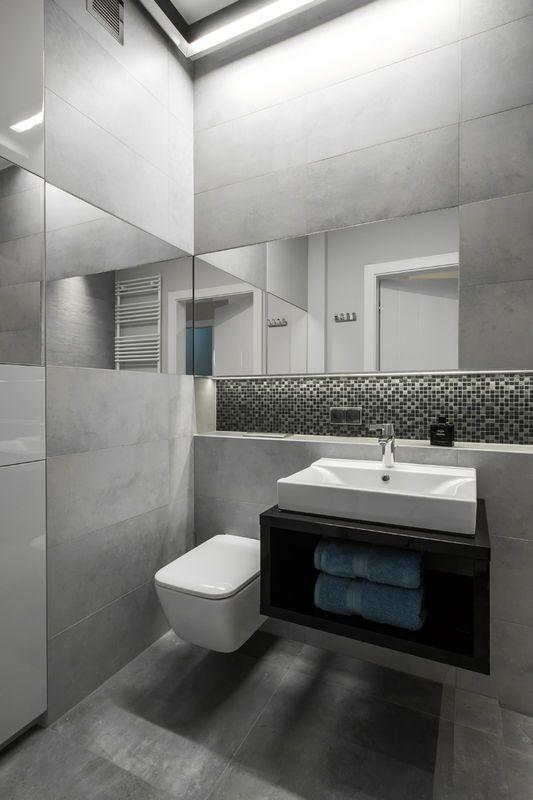 Dla przełamania monotonii szarości w tej łazience niszę-półkę nad umywalką wyłożono szklaną mozaiką. Z kolei lustra na dwóch ścianach dały powiększający efekt. Jedno z nich zostało zintegrowane z frontem łazienkowej szafy.