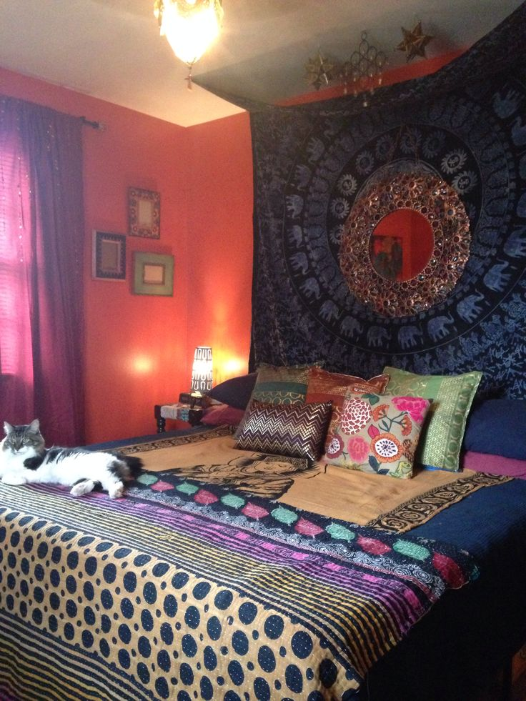 Bohemian/Indian/Moroccan style bedroom. DIY tapestry headboard. Jewel tone color scheme. Cayenne orange walls. Master bedroom design by Heather Tostenrude.