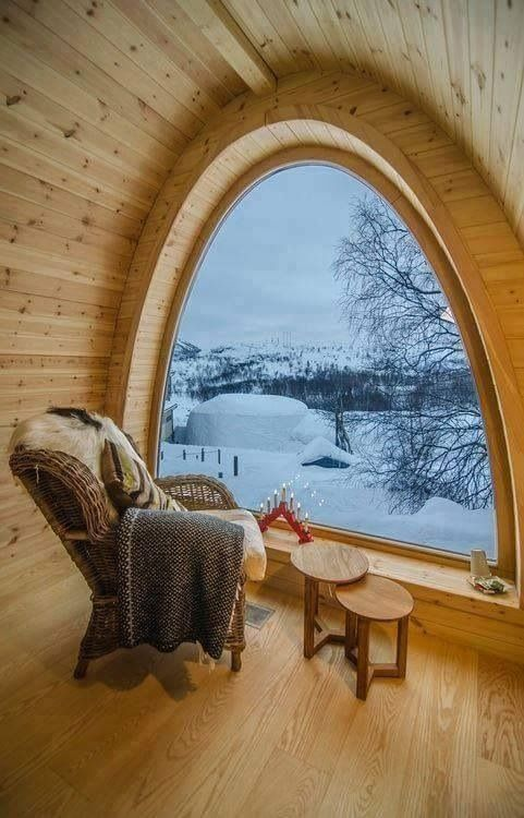 chair in front of half circle window in wood cabin look out into snow covered trees