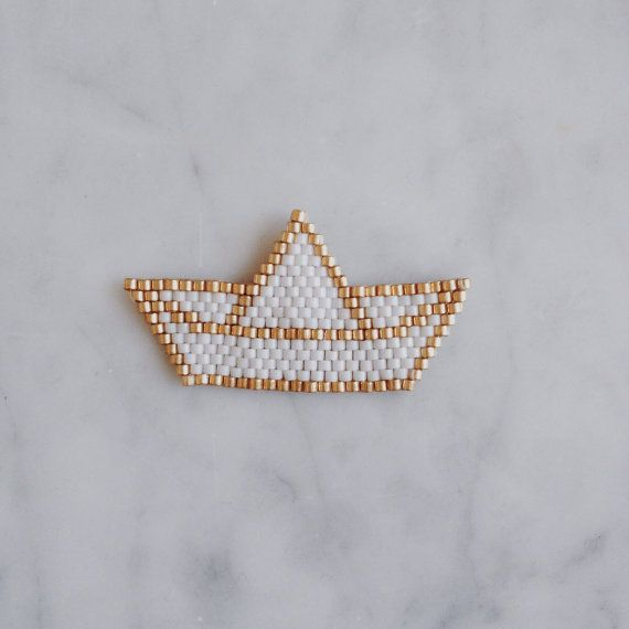 Cette broche blackpearl© est confectionnée avec des perles miyuki et représente un bateau en origami. Elle est constituée de 243 perles miyuki delicas 11/0 et entièrement brodée main. Les perles miyuki delicas sont des perles de verre japonaises réputées pour être trés régulière. Une attache est collée au dos pour pouvoir la porter en broche.  Dimensions : 4,5 x 2,3 cm Couleur blanc et dorée. Existe en jaune et dorée ou vert deau et dorée. Possibilité de la réaliser avec une autre couleur…