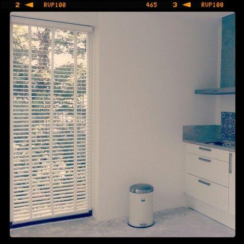 Windowdressing. Witte houten jaloezieen.