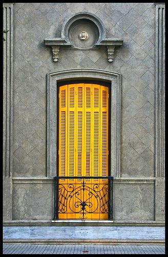 Vivid yellow door pops against the grey building.