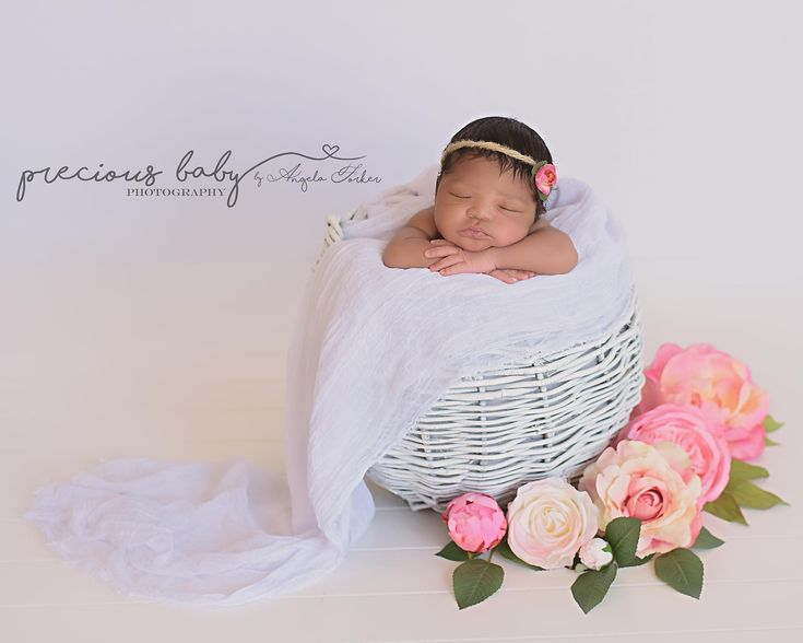 Gorgeous newborn african american baby girl sleeping in a white basket surrounded by beautiful pink flowers