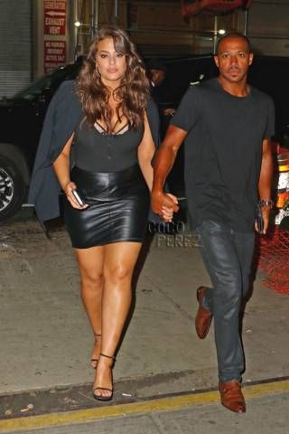 Ashley Graham - faux leather mini skirt with tucked in black shirt with interesting neckline paired with strappy heels