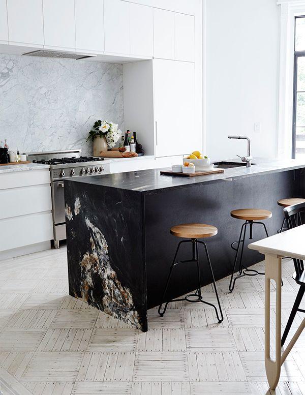 Une cuisine blanche, épurée et chic, avec un îlot en pierre noire qui contraste.