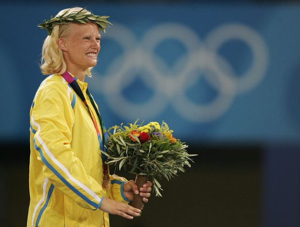 Carolina Kluft Photos - Gold medalist Carolina Kluft of Sweden celebrates on the podium during the medal ceremony of the women's heptathlon event on August 21, 2004 during the Athens 2004 Summer Olympic Games at the Olympic Stadium in the Sports Complex in Athens, Greece. Austra Skujyte of Lithuania came second and Kelly Sotherton of Great Britain came third. - Olympics Day 8 - Athletics