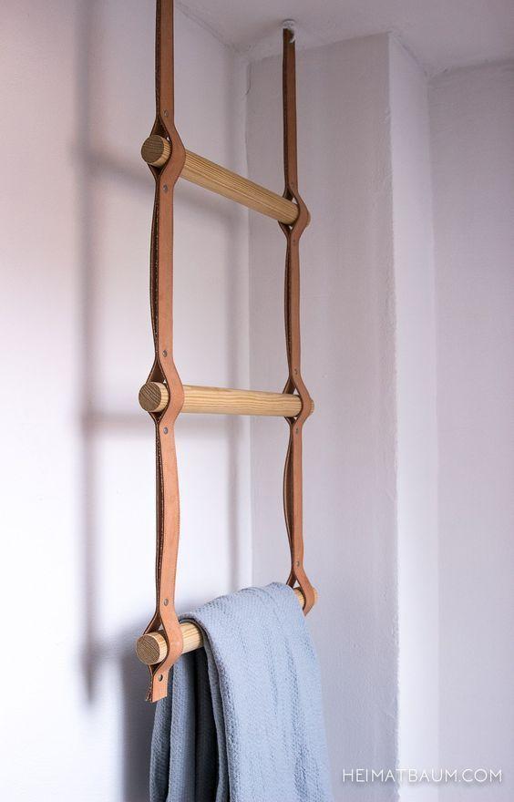 Un porte serviette échelle avec des barreaux de bois sur des sangles de cuir
