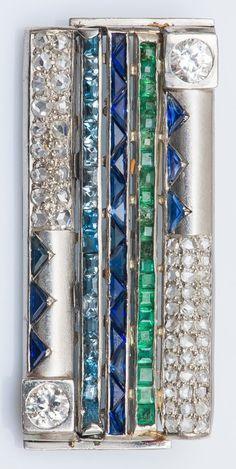 Broche rectangulaire en or gris 18 carats (750 millièmes) à motifs géométriques sertis d'un pavage de diamants taillés en rose, de deux diamants plus importants de taille ancienne, d'une ligne d'émeraudes calibrées, d'aigue-marines calibrées et de saphirs taillés en triangle. Travail étranger époque Art Déco.