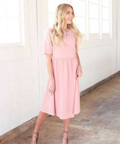 The Natalie dress features a relaxed silhouette with flattering elbow length sleeves, available at Omika!