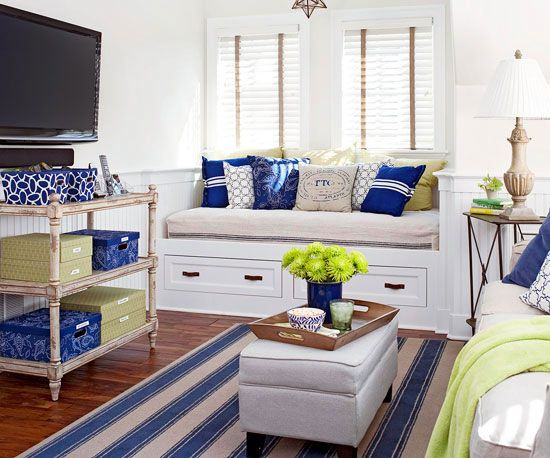 Decorated in crisp white and blue with pops of spring green, the inviting open living area not only serves as living, dining, kitchen, and work space -- it can also host up to three guests thanks to a trundle bed/bench squeezed into a window niche and a traditional pullout sofa. An ottoman serves as a coffee table with hidden storage beneath its upholstered lid.