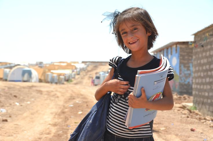 A Syrian Kurdish refugee child comes back from school in Domiz refugee camp in…