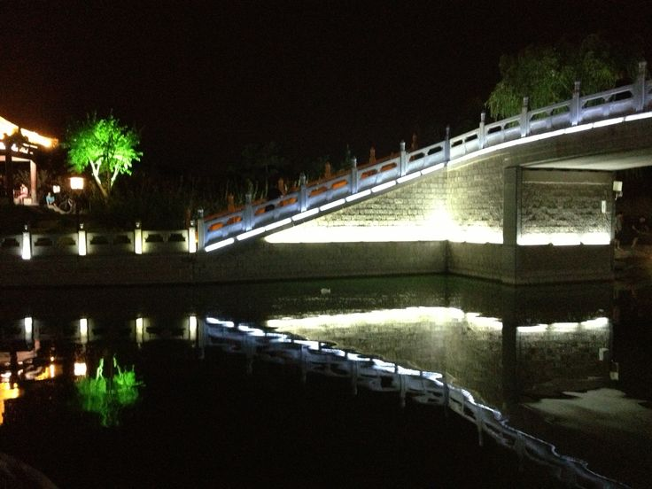 One scene of a bridge looked beautiful at night. The water looks like a magic Mirror. Shadow's clearly reflecting as an art piece.