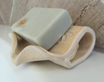 Hand built ceramic self draining soap dish is perfect for your artisanal hand crafted soaps. The dish is angled so that excess moisture from soap drains into sink rather than pooling in the dish. This greatly increases the lifespan of hand crafted soaps. Dish can be popped into the dishwasher for easy cleaning.  Soap dish is approximately 5 deep and 4.5 wide and will work with all soap shapes. Dish is glazed in a combination of Bone and Waterfall Brown.  Featured in the dish is green clay…