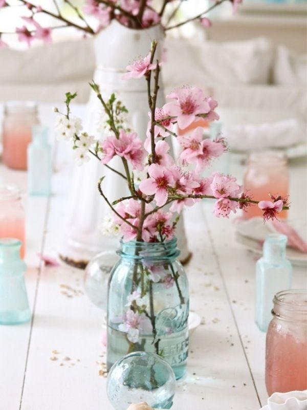 décoration mariage en branches de cerisier fleuri et pots en verre