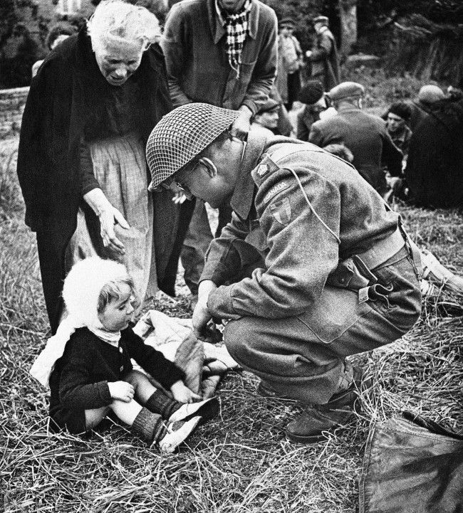 A Canadian soldier, serving with the British forces in Normandy, strikes up an acquaintance with a little French girl on september 7, 1944, one of a group of refugees that were fed by the liberating armies. The feeding arrangements were organized by the Civil Affairs. (AP Photo)
