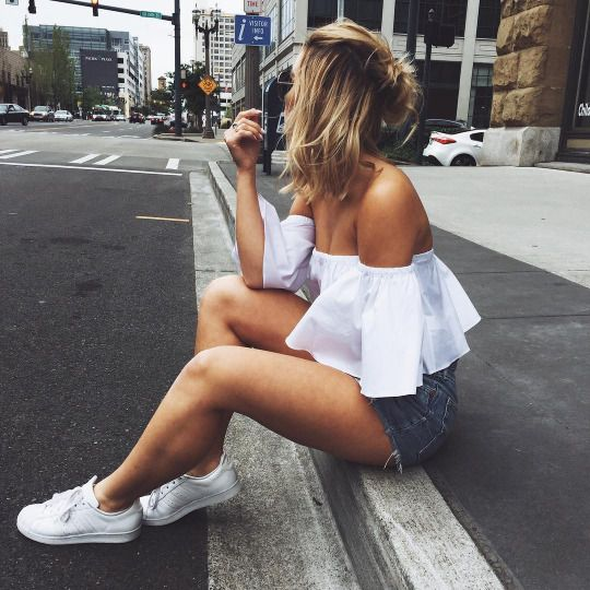 White off shoulder top and white sneaks with denim shorts and half bun half down
