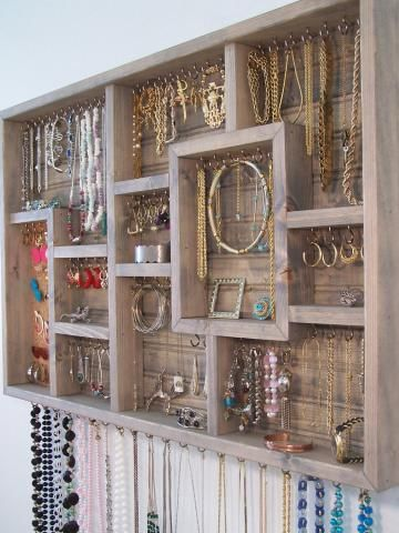 Get a collage picture frame, remove glass, insert screw in hooks to hang jewelry.