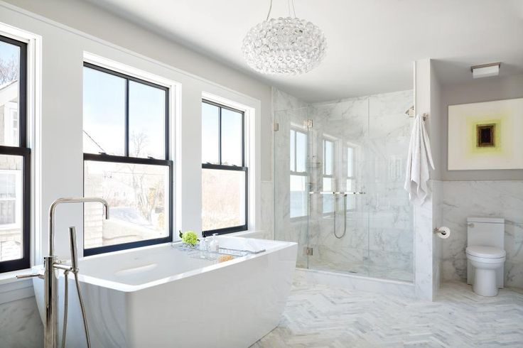 Simple black frame windows allow ample natural light to flood this white bathroom, enhancing the bright, airy feel. Marble wainscoting and tile floors give the space a luxurious, classic look. A contemporary bathtub and pendant light offer fresh, stylish touches.