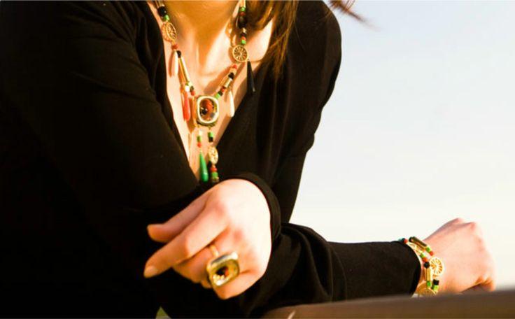 Parure in oro giallo lucido con particolari in onice, corallo e turchese verde. Cordoncino in velluto nero.