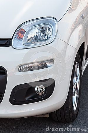 A closeup of the right headlights, part and wheel of a brand new white car.
