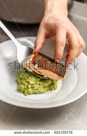Chef is serving grilled salmon over a bead of green risotto rice